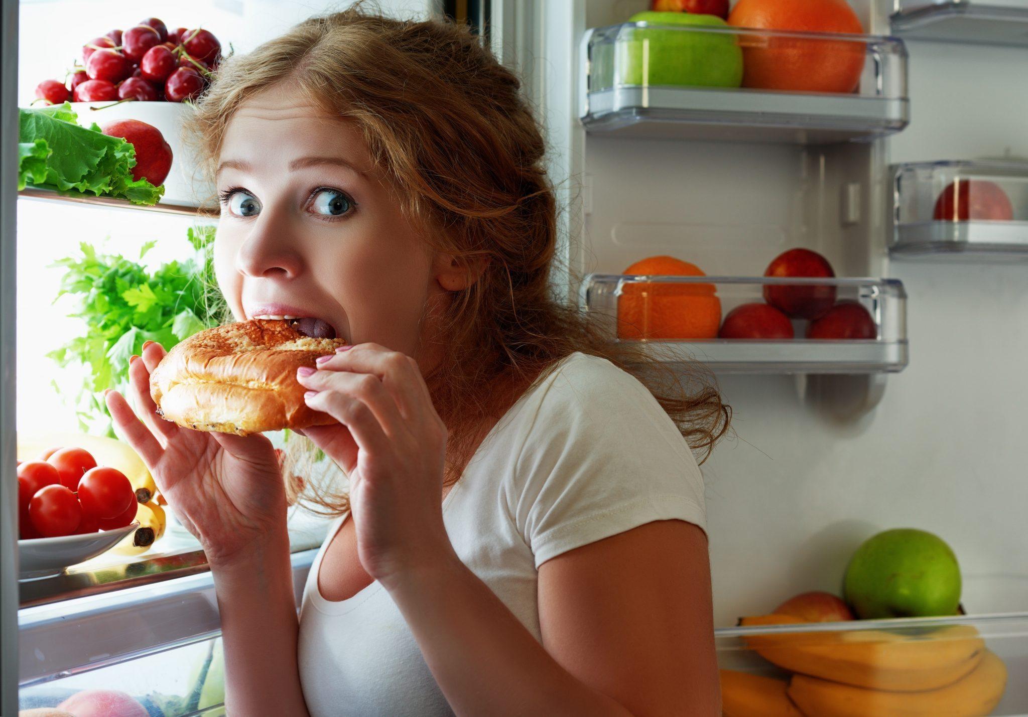 Девушка ест булочку у холодильника